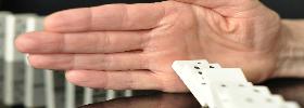 immagine di una mano che ferma dei mattoncini del domino